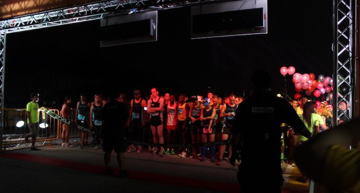 Totally dark at the start line, crowd of people illuminated on the line