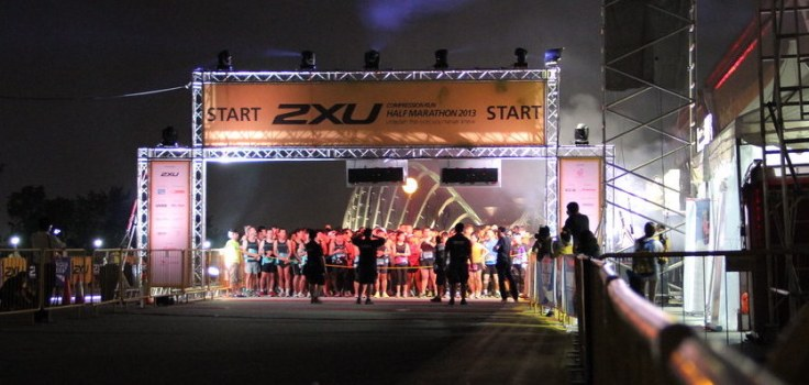 View down the road to the start line, runners wait under the 2XU gantry