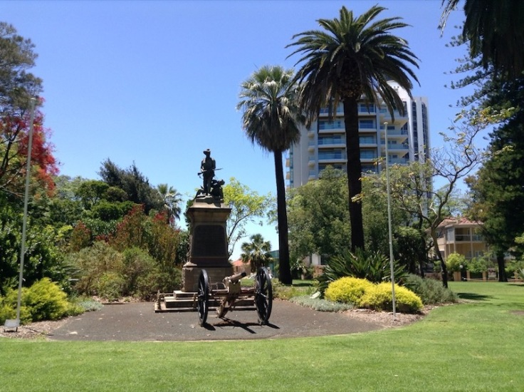 Statue of soldier on a plinth and cannon in front, with grass and shrubs all around, in bright sunshine.