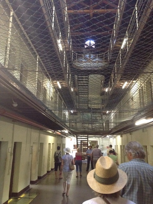 Inside the prison; netting above the ground floor to catch items thrown, narrow walkways to cells above