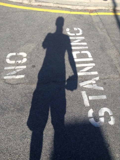 "My shadow, over a ""No standing"" sign painted on the road"