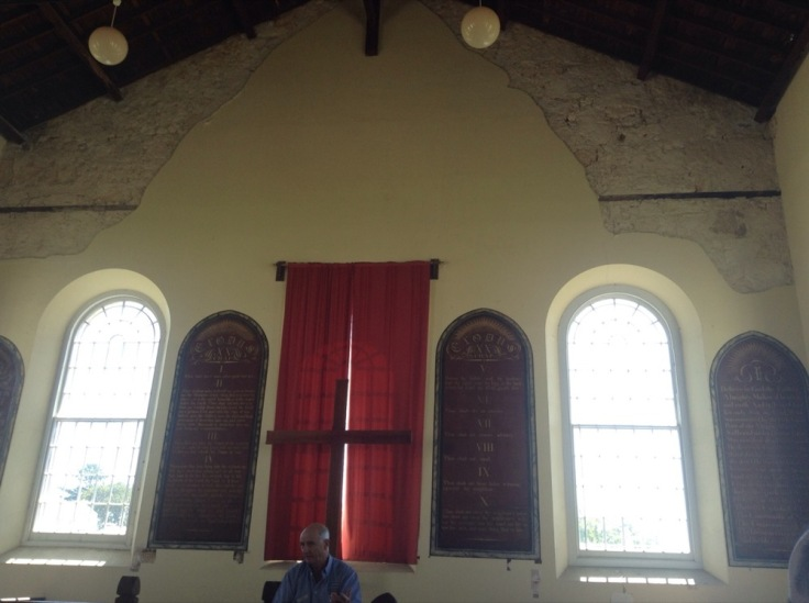 The chapel, filled with light. Plaster has peeled from the top. A red curtain hangs over one window; two others have no curtain