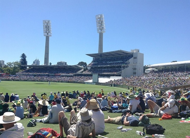Crowd lying on the grass at the WACA. Floodlights are unused above the stands opposite, in bright, hot sunshine
