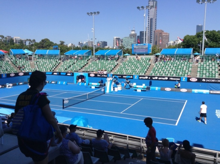 Empty seats around show court 2, its surface a vivid blue