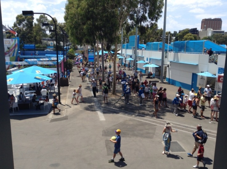 People enjoying shade on the concourse behind a show court