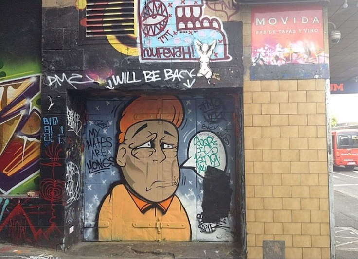 A mural on a wall; man in a shirt with orange quiff, and a speech bubble