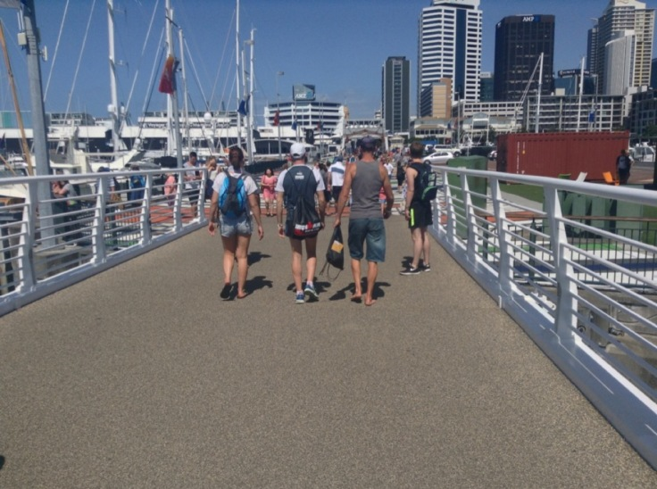 People walking across a bridge by the marina, one with ironman bag to prove what he's there for
