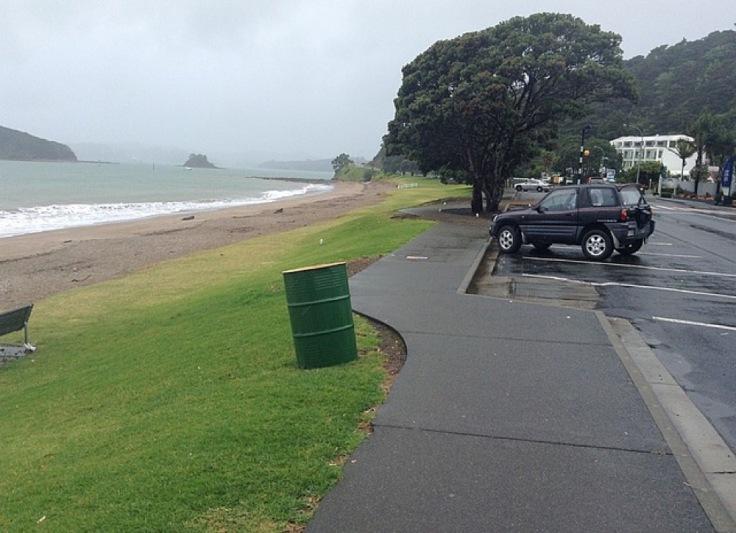 A car parked by a rainswept beach