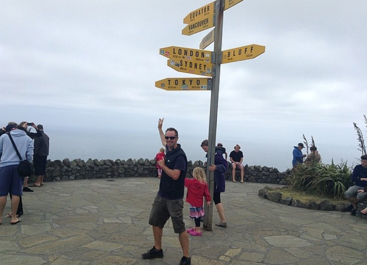 Me at the cape, pointing to a sign with labels for London, Sydney, Tokyo, Bluff, Equator, Vancouver all visible