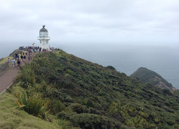 People thronging around the lighthouse, with the ground dropping away to either side, giving a view over the sea