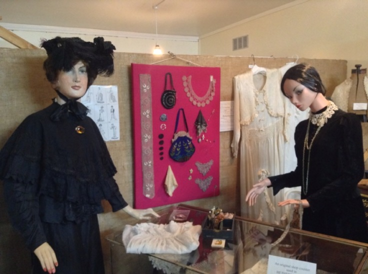 Posed tableau from a shop, with mannequins, from times past. Handbags and jewellery hang on the wall