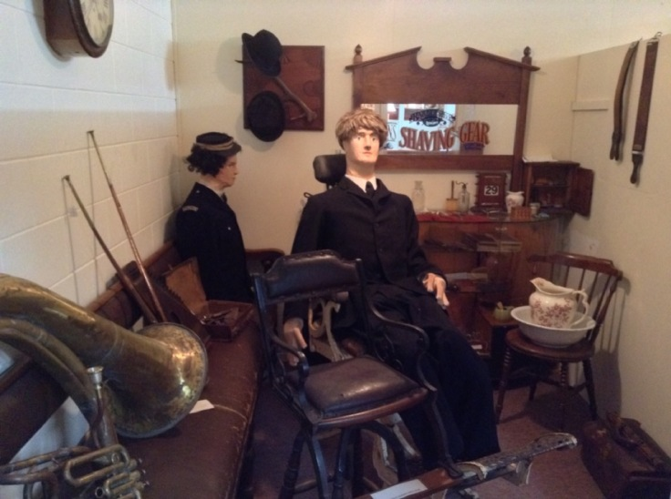 More terrifying dummies. One is sitting, apparently unnoticed, behind the other, in a barber shop