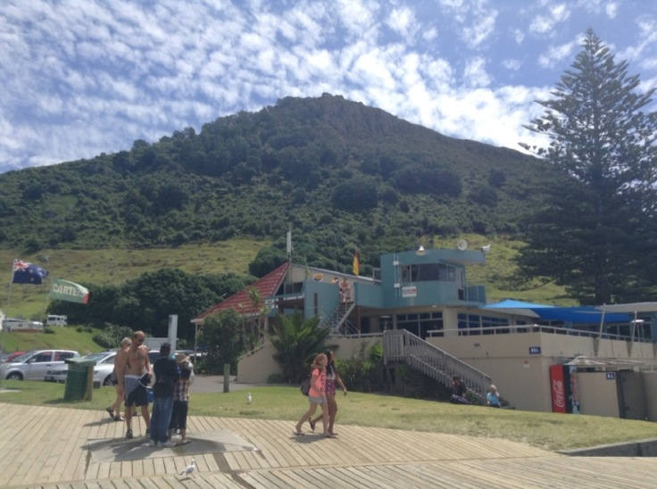 Looking up at Mount Manganui, as people walk on a boardwalk in front of it
