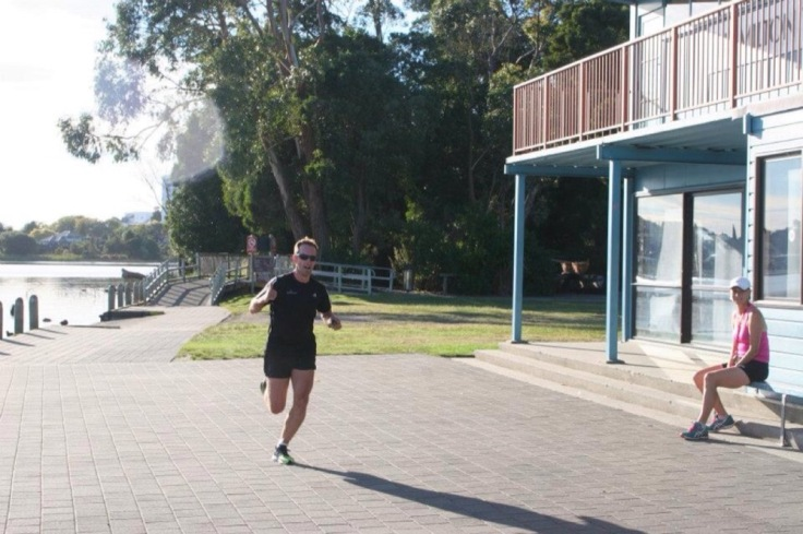 Me, running past the clubhouse, with the lake visible on the left, trees behind