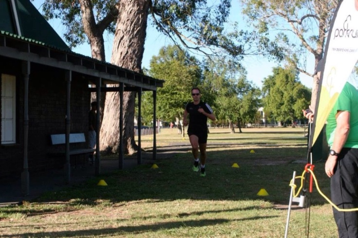 Crossing the finish line, a parkrun flag next to the camera