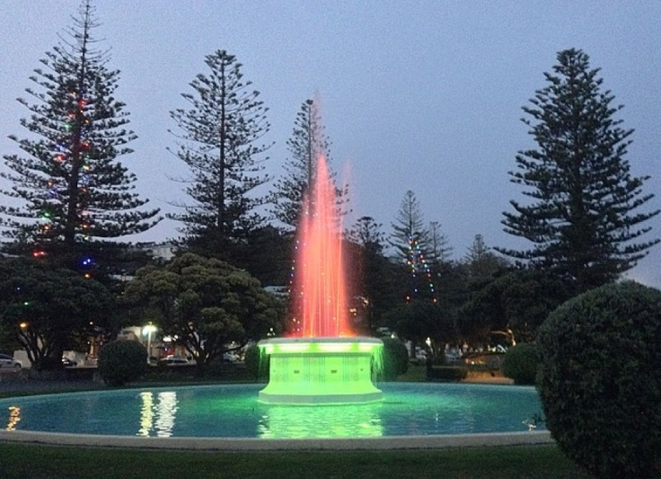 A fountain is lit up as night falls, with a bright green plinth and red light through the water