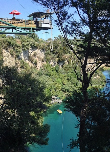 A bungy rope hangs from a platform, high above the river