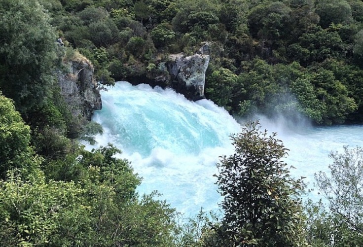 Low but wide, pale blue water rushes through the falls
