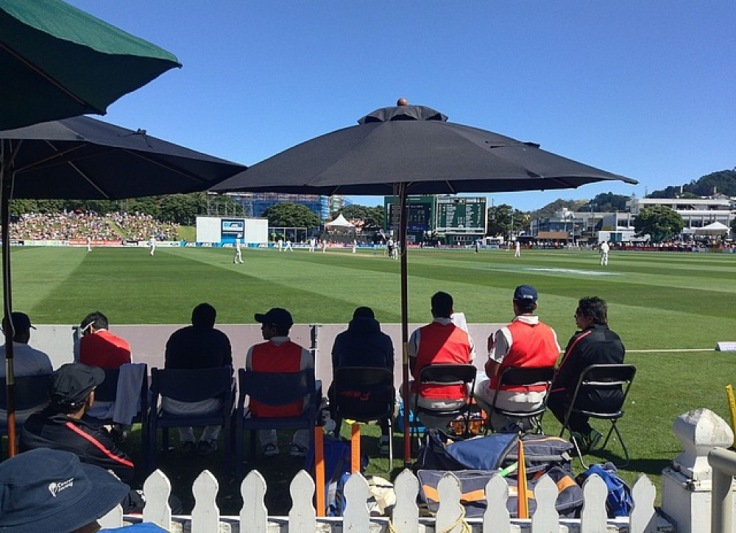Substitute players sit under the shade of two large umbrellas, watching the play