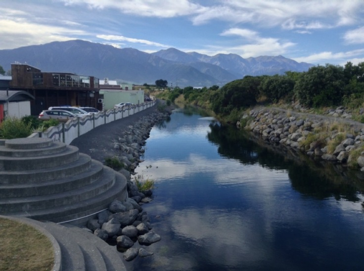 A river wends through town, mountains behind