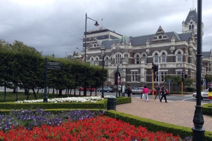Flower beds outside the station. Red, then purple, then white flowers, in separate beds
