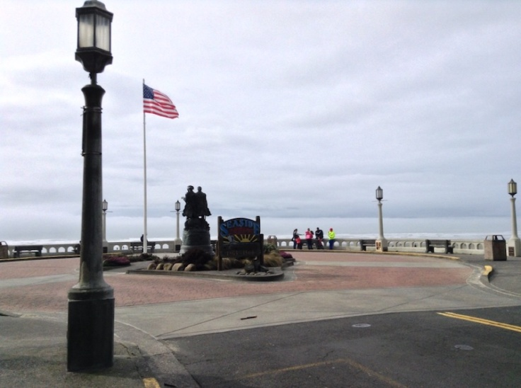 Promenade at Seaside, Oregon, with the US flag flying above a couple of statues