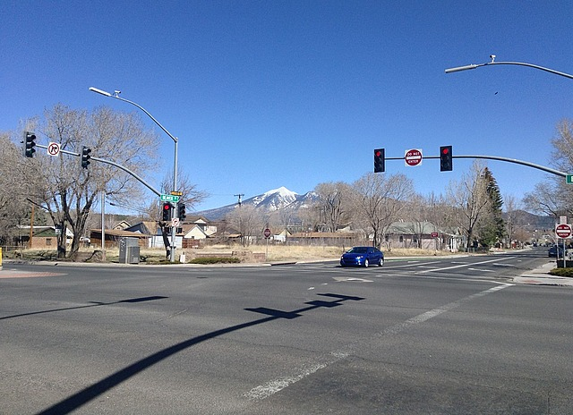 An intersection, with a snow-capped mountain behind, under a blue sky