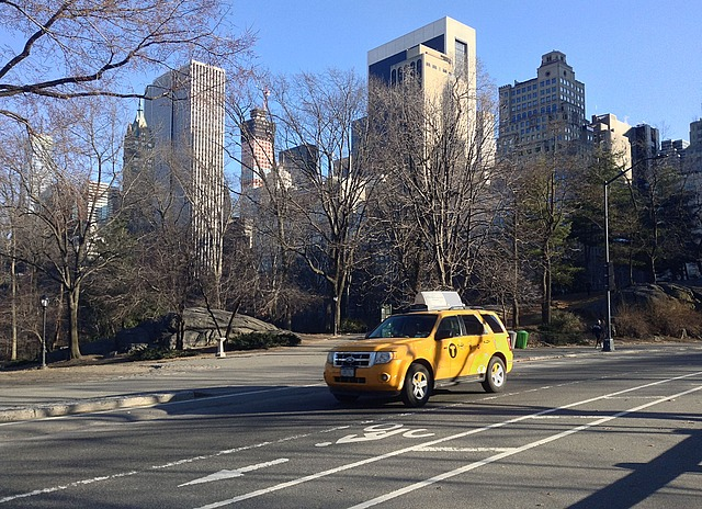Yellow taxi in front of skyscrapers