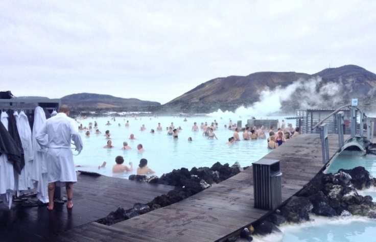 Lots of people bathing in the Blue Lagoon. Mountains behind.