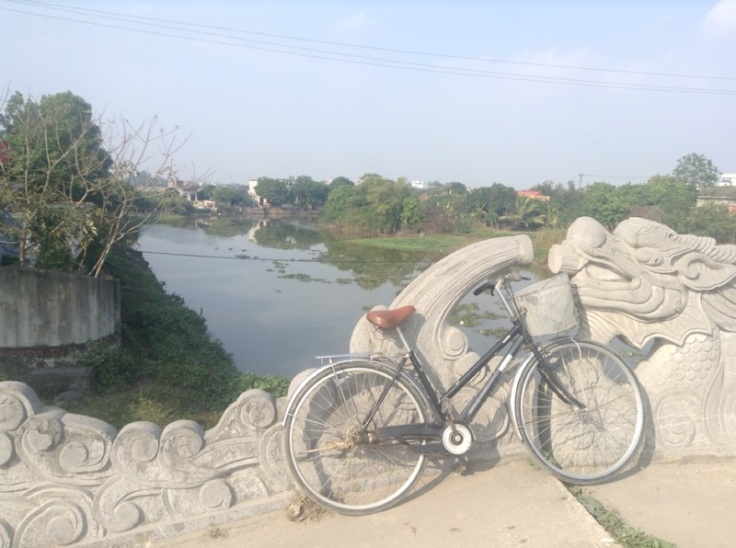 My bike, leaning against ornate carvings on a stone bridge