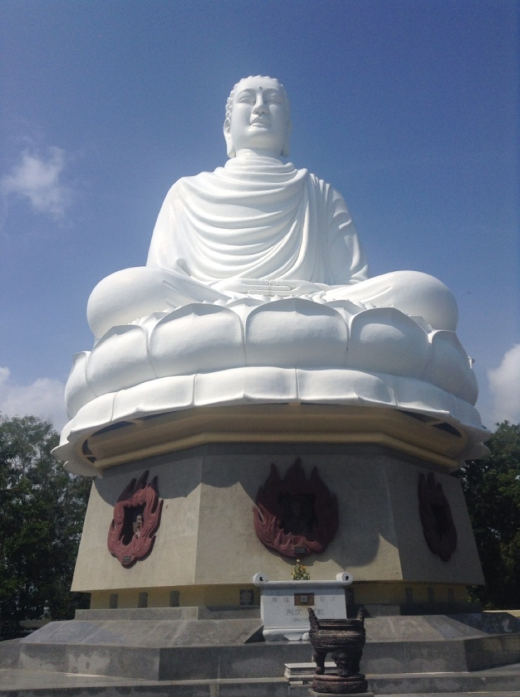 A large white Buddha on a plinth