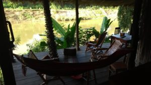 A hammock and several bamboo deck chairs overlooking the river