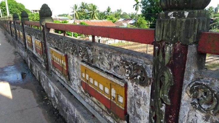 Train carriage relief murals decorate the bridge at Bago