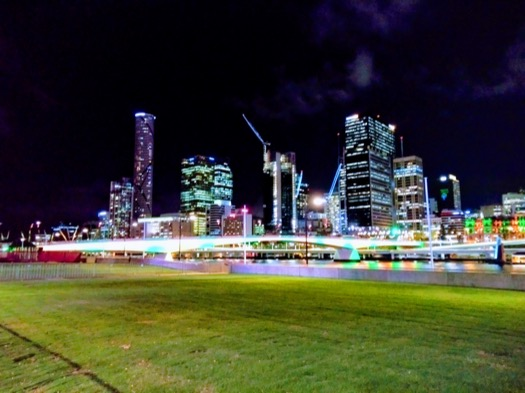 Lights of many colours on the riverfront, plus the skyscrapers behind are lit up
