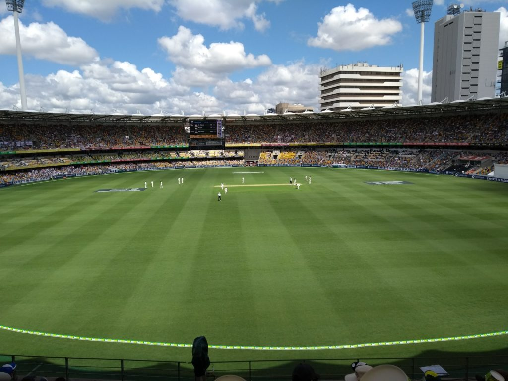 View of the pitch from the Gabba. Play in action, looking very far away.