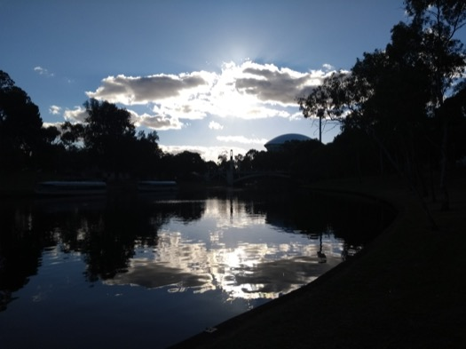 Bright sun shining through clouds, reflected on the Torrens river
