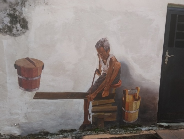 Wall art (man working at bench, painted onto wall)
