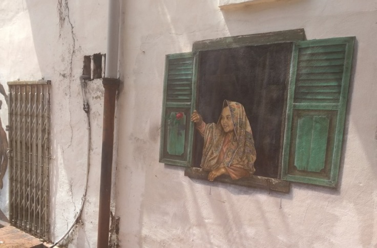 Wall art, Melaka (girl leaning out of window, painted onto wall)