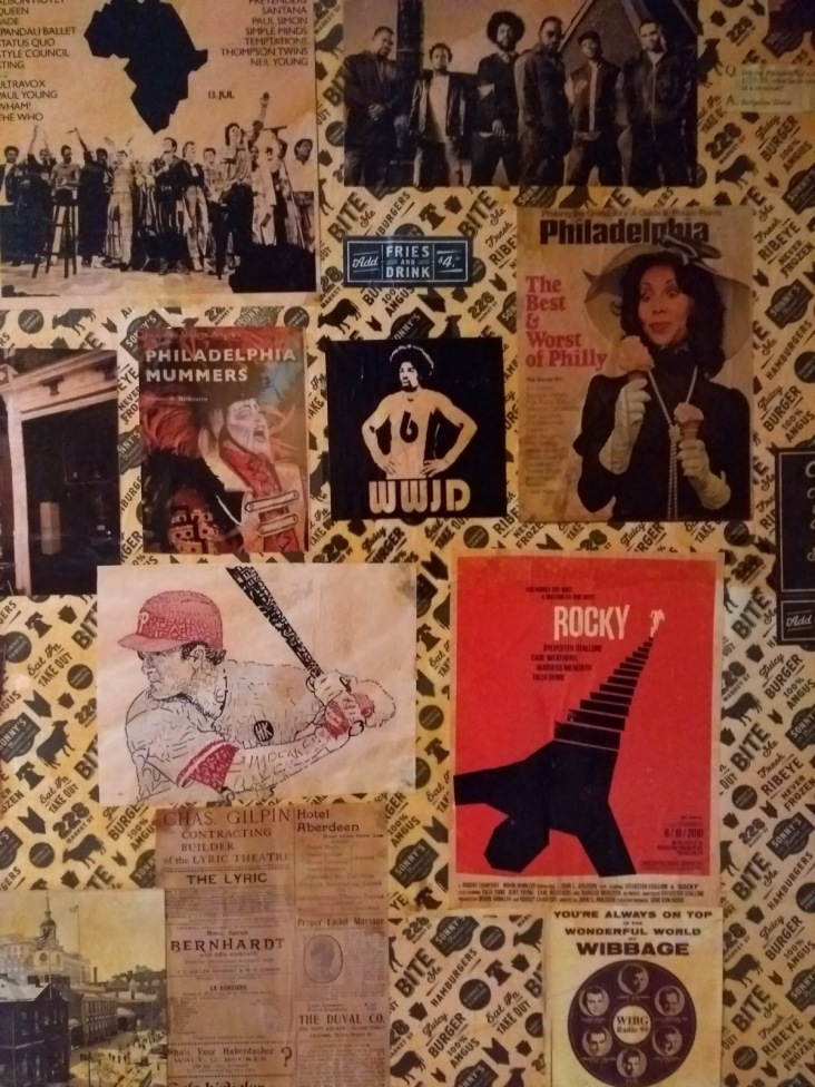 Collage of posters and adverts, in a bar
