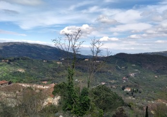 View of cloudy blue sky and dark green rolling hills from Montecatini Alto
