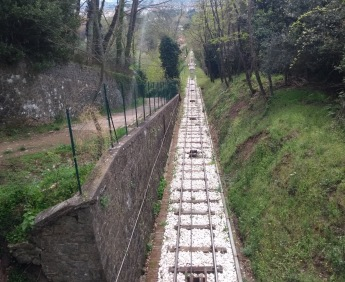Funicular track disappearing below a stone bridge