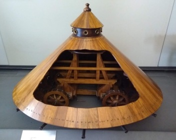 Wooden tank, pyramid in shape, with wheels covered by the 'skirt' and a turret