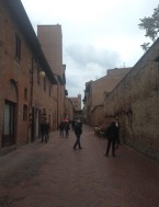 Via Boccaccio. Old brick buildings, some rebuilt after WW2 damage, line the sides