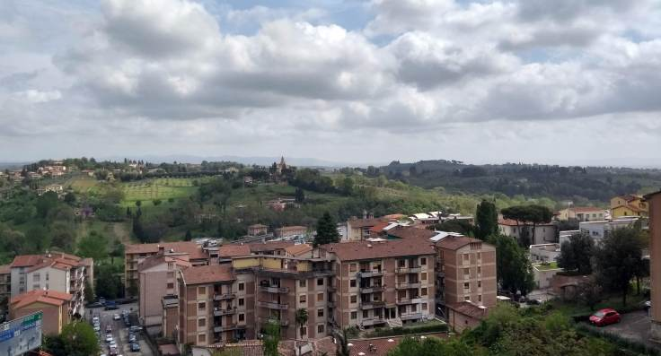View over unlovely Siena flats, to green fields and forested hills beyond