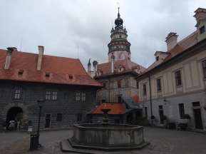 Courtyard in the Castle, ornate circular tower behind two-storey buildings.