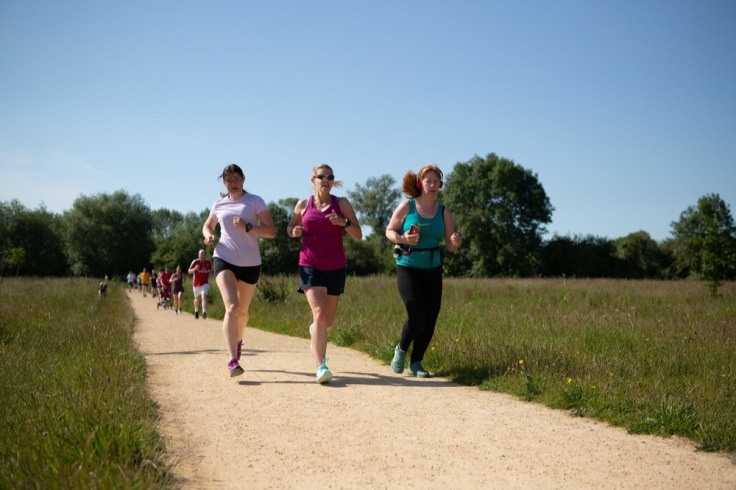 3 female runners moving along the path