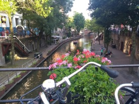 A bike and flowers overlook a canal