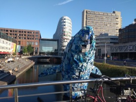 Whale sculpture rises out of a canal near the central station