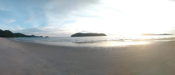 Sandy beach panorama, low sun glinting on a flat sea, with a small island in the centre of the view.