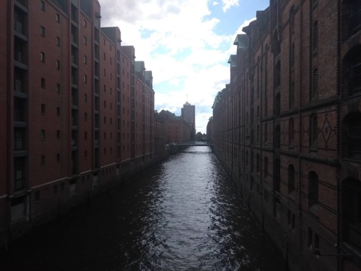 Large, long, buildings dominate both sides of a canal
